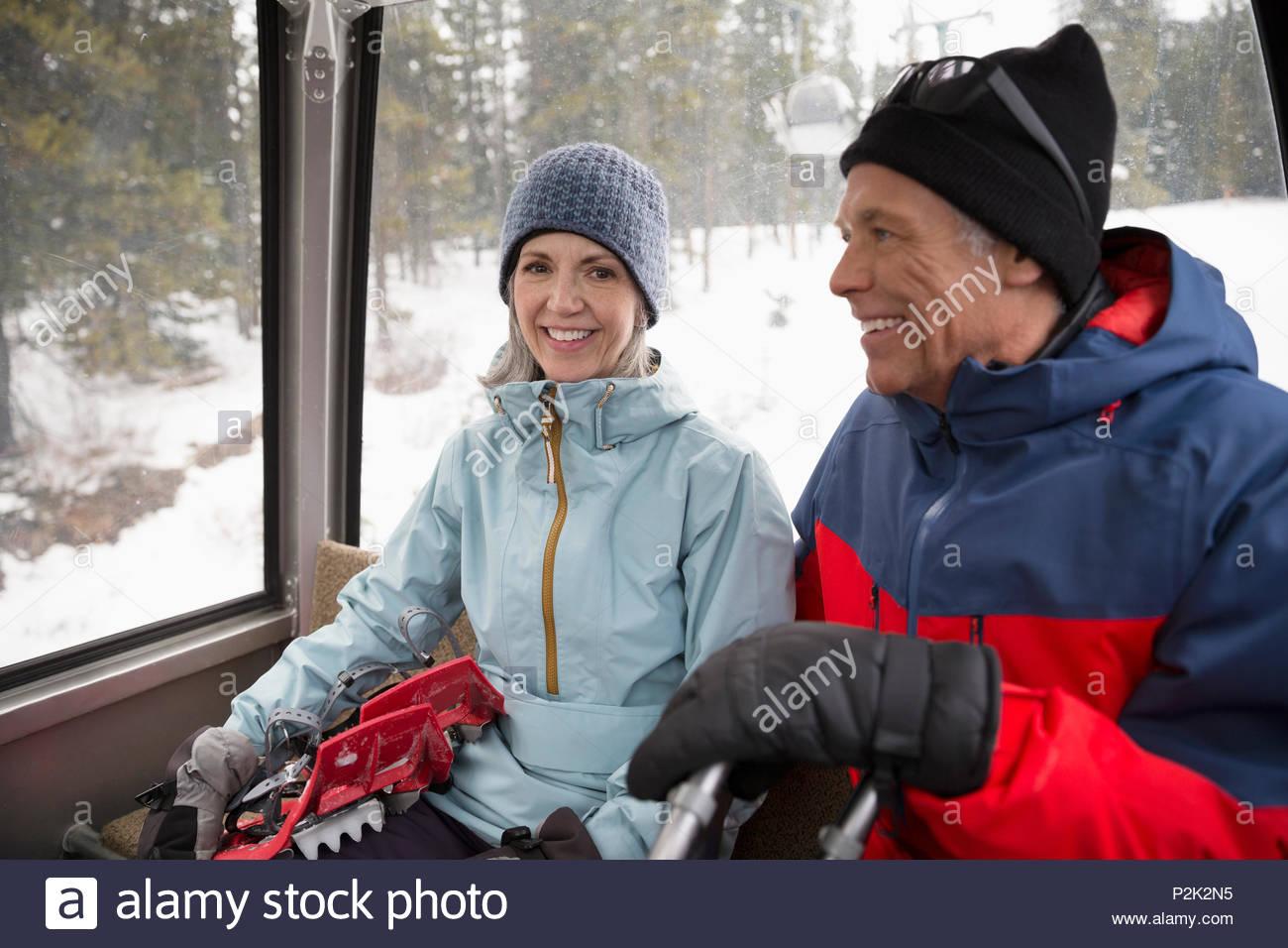 Active senior snowshoer couple riding gondola - Stock Image