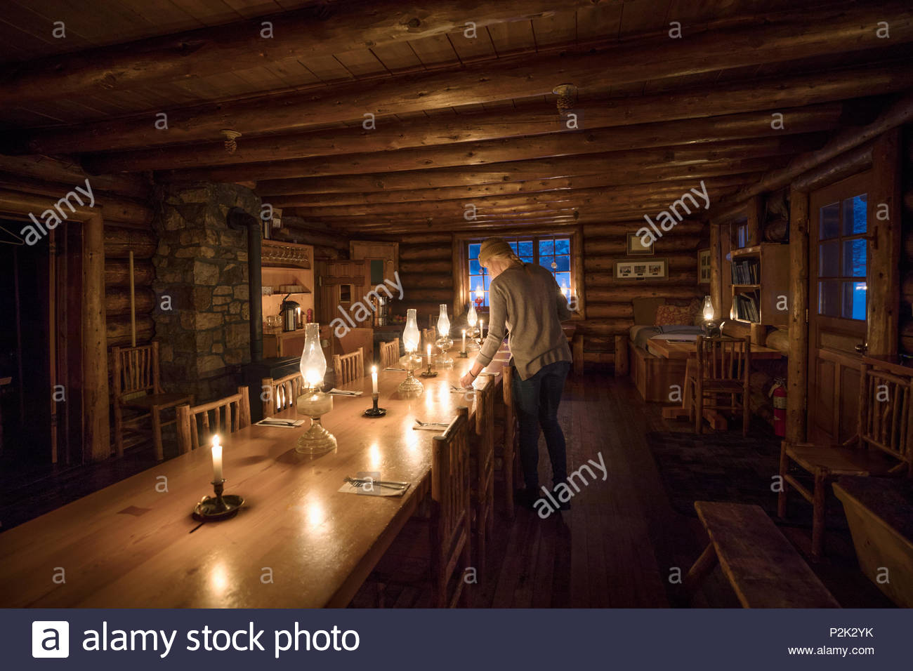 Woman preparing candlelight dining table in ski resort lodge - Stock Image