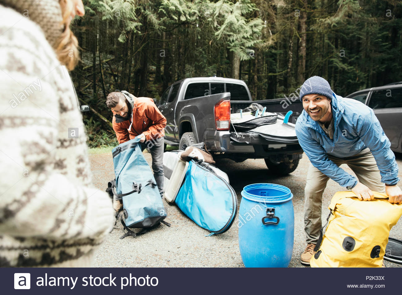 Friends on weekend surfing getaway, unloading equipment in parking lot - Stock Image