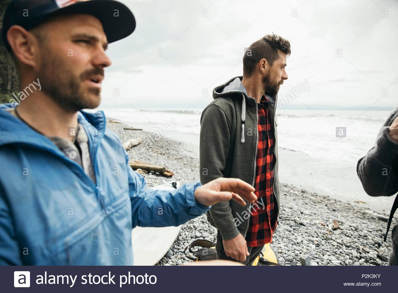 Men friends enjoying weekend surfing getaway on rugged beach - Stock Image