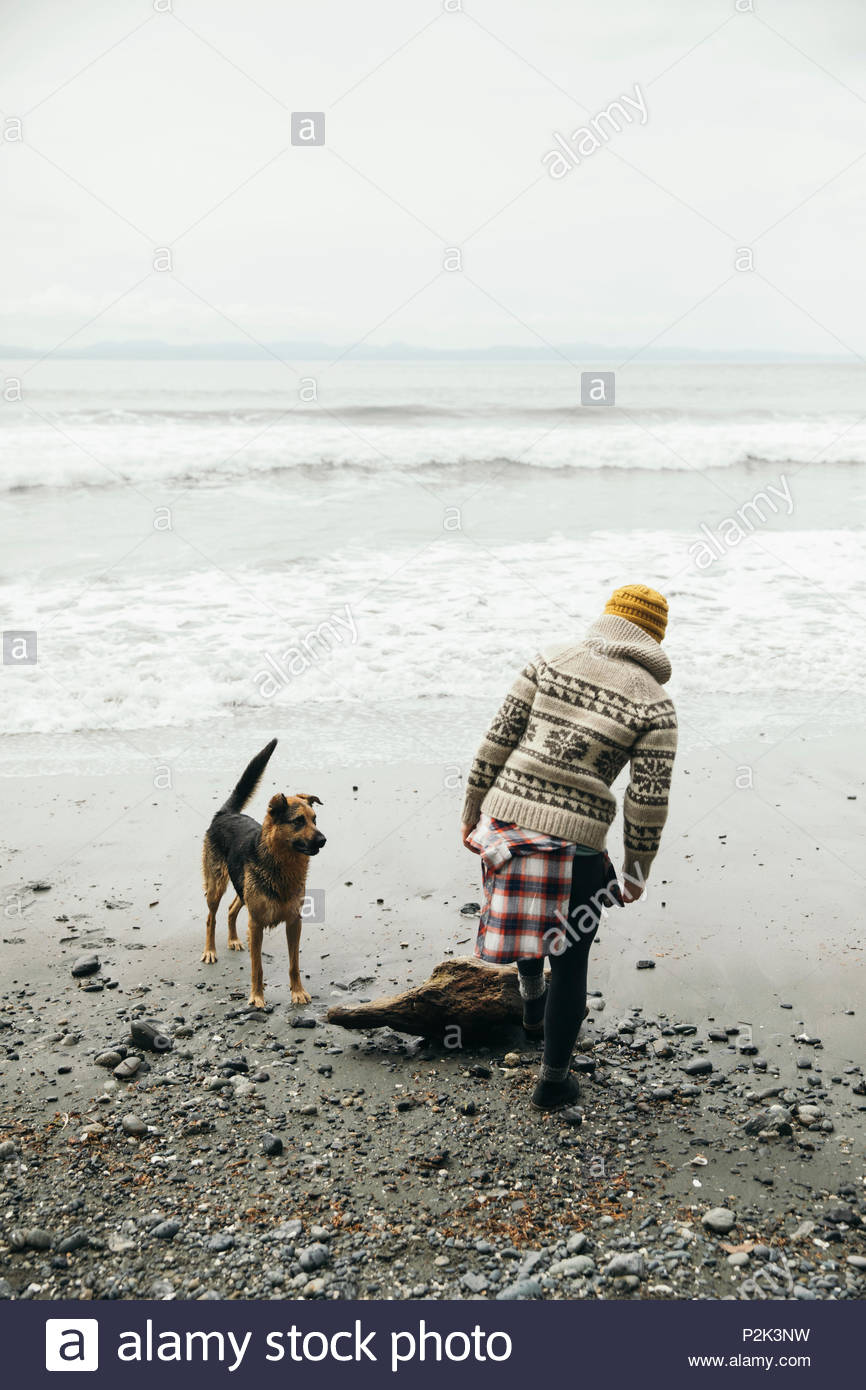 Woman with dog on rugged beach - Stock Image