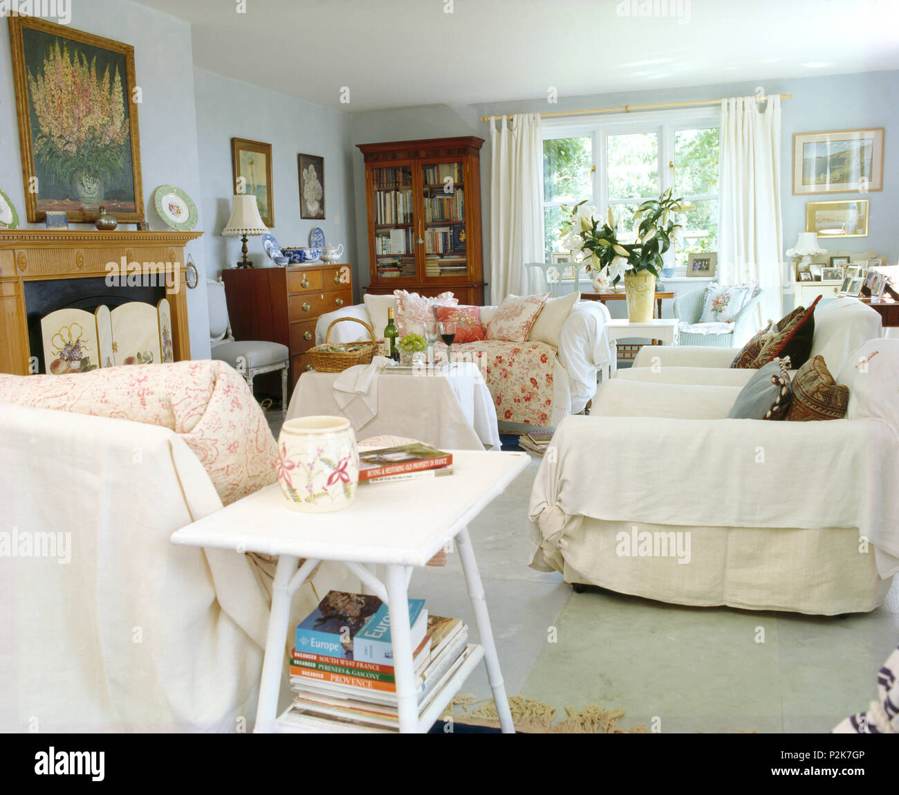 Small white painted table and sofas with quilted throws in cottage ...