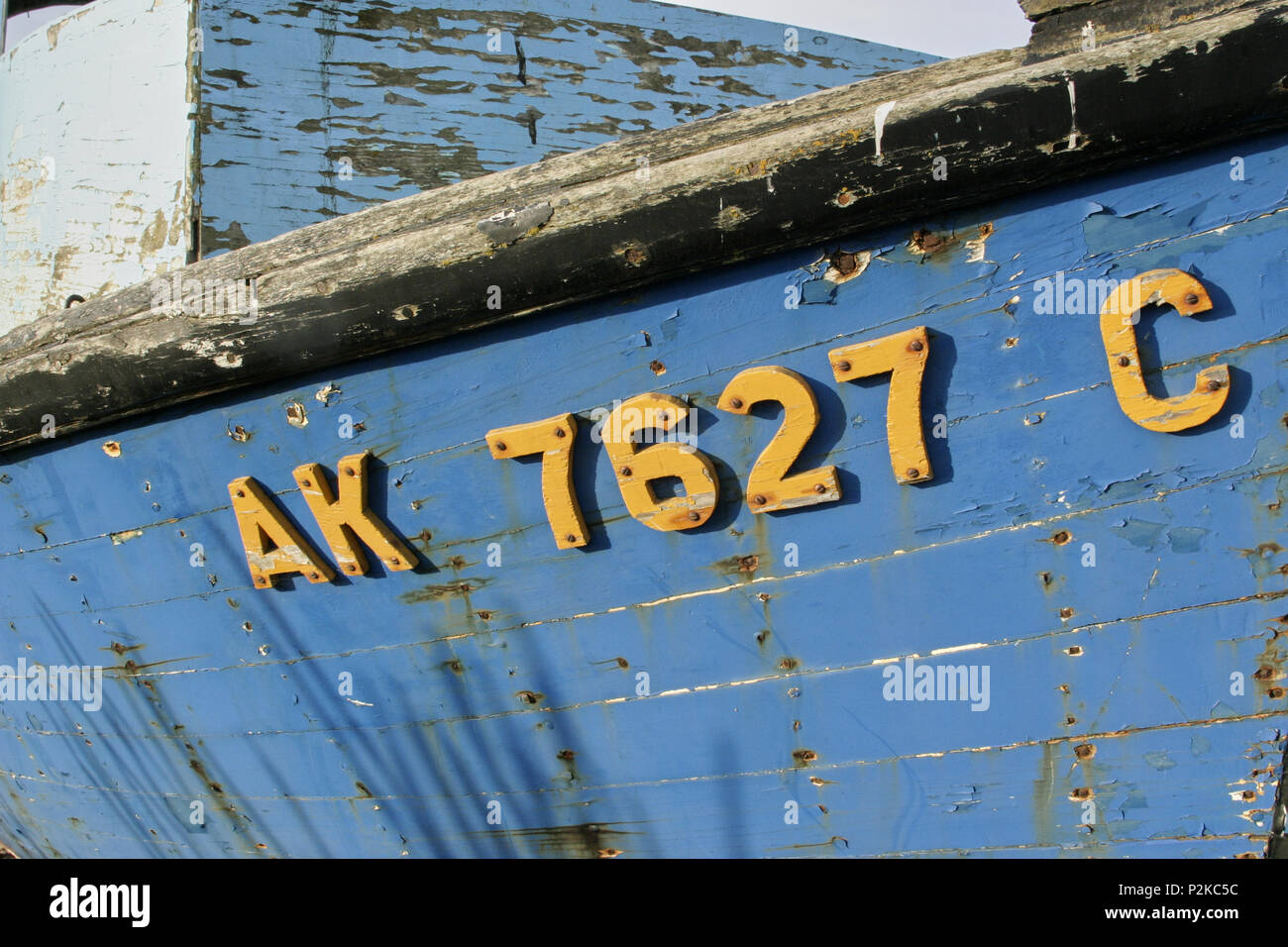 Old weathered wooden fishing boat with yellow registration letters ...