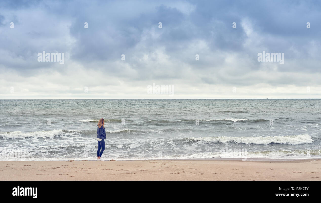 Woman walking along the edge of the surf on a beach in a blue denim outfit looking out to sea on a cold cloudy day with copy space - Stock Image