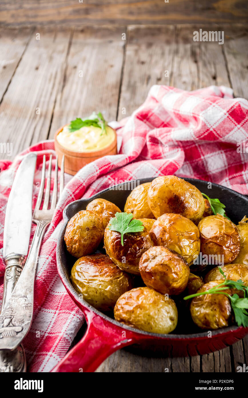 Baked in frying pan whole young potatoes, homemade vegetarian food, wooden old rustic table, with sauce, copy space Stock Photo