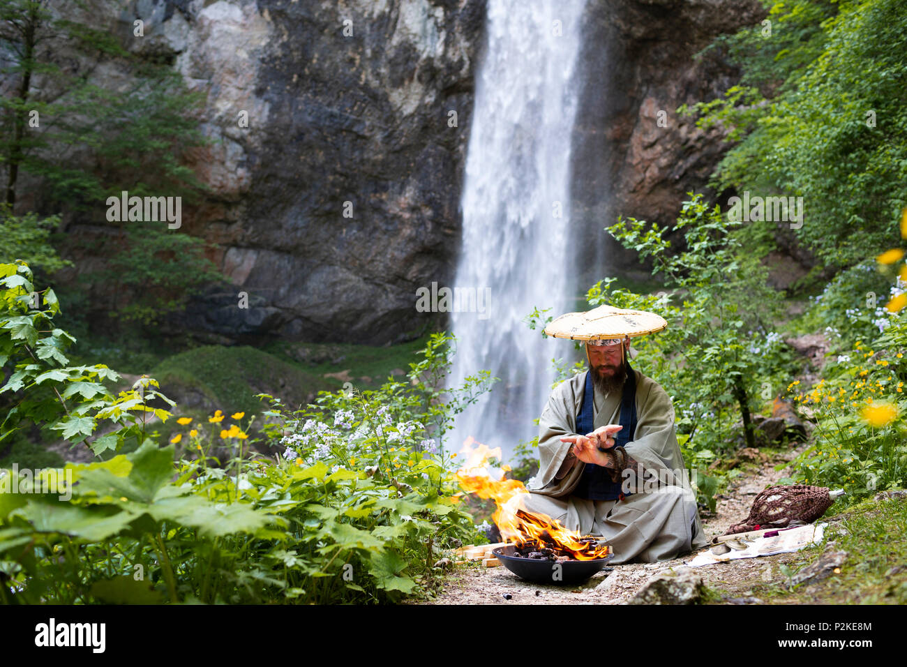 European man with beard and japanese robe makes fire ceremony in front of Great Waterfall in Austria - Stock Image