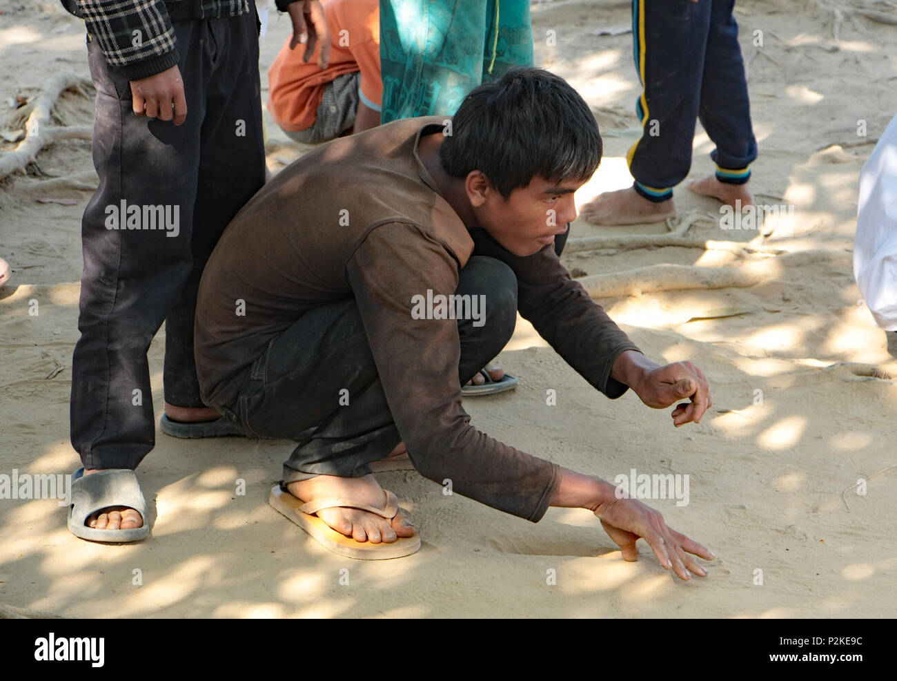 A Cambodian boy crouches on the ground playing a game of Marbles concentrating as he flicks the ball into play. In the playground of Ream School. - Stock Image