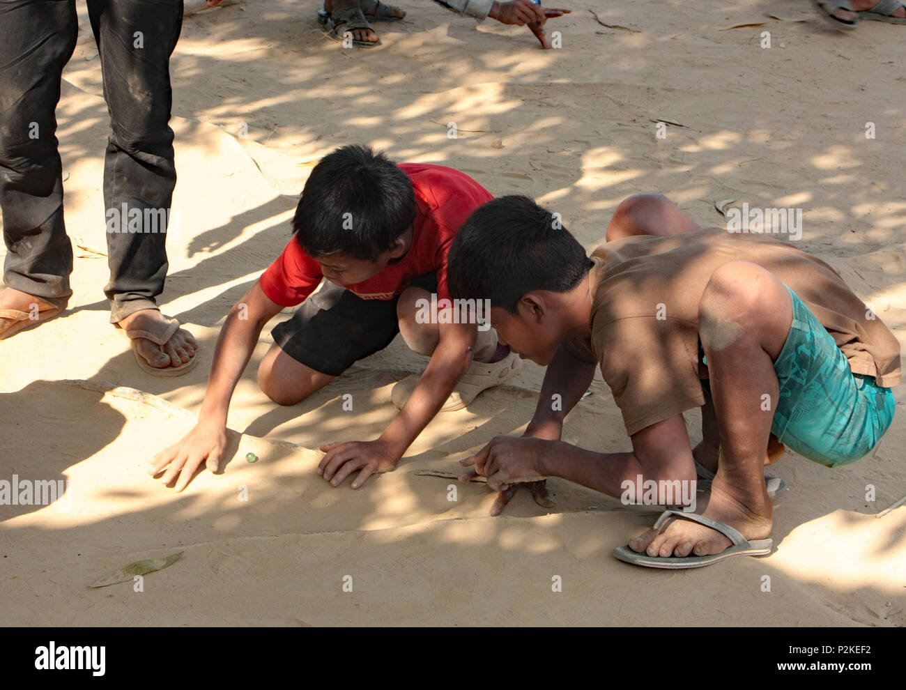 Two Cambodian boys playing the game of Marbles, with small glass balls, on the rough sandy earth of Ream School playground. - Stock Image