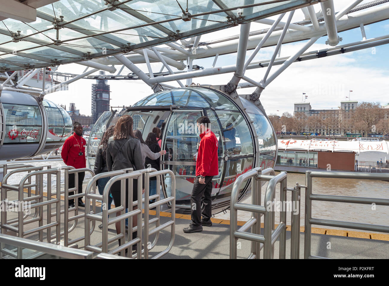 Passengers queuing to board a capsule of the London Eye, a popular giant Ferris wheel, iconic landmark of London, located by River Thames in London - Stock Image