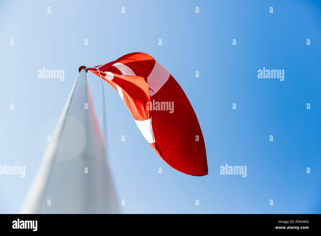 danish flag blowing in the wind, Baltic sea, Bornholm, near Gudhjem, Denmark, Europe Stock Photo