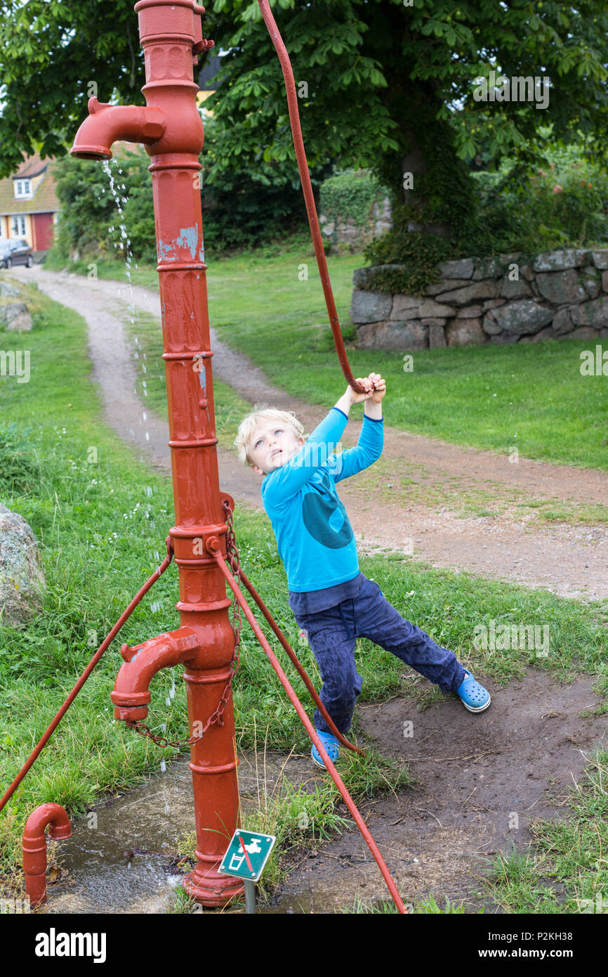 5 year old boy pumping water with a traditional water pump, Baltic sea, MR, Bornholm, Svaneke, Denmark, Europe - Stock Image