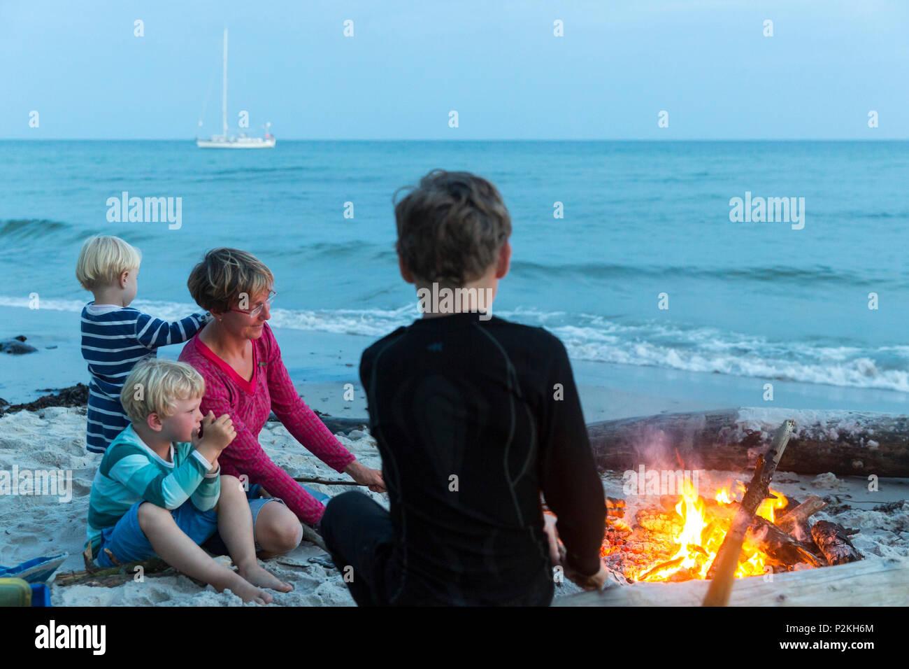 Familiy with children sitting around the campfire, adventure, sailing boat, dream beach between Strandmarken und Dueodde, sandy - Stock Image