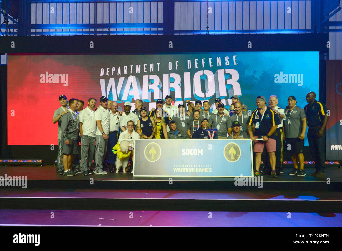 Team SOCOM celebrates on stage during the 2018 Warrior Games closing ceremony held at the Air Force Academy in Colorado Springs June 9, 2018. Created in 2010, the DoD Warrior Games introduce wounded, ill and injured service members and veterans to Paralympic-style sports. Warrior Games showcases the resilient spirit of today's wounded, ill or injured service members from all branches of the military. These athletes have overcome significant physical and behavioral injuries and prove that life can continue after becoming wounded, ill or injured.  (Photo by Michael Bottoms, USSOCOM Office of Com Stock Photo