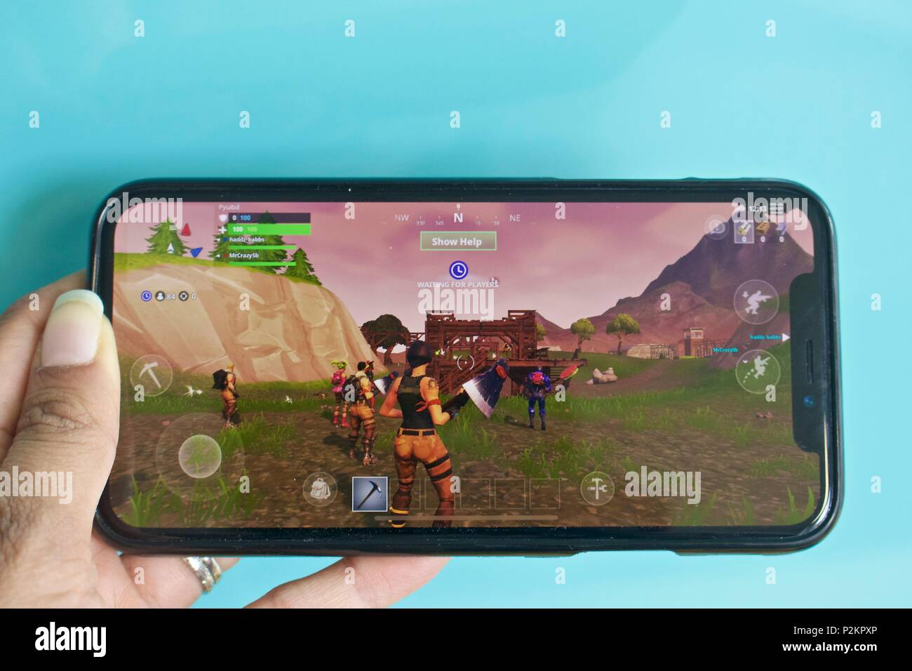 a female playing the number 1 top grossing mobile game fortnite battle royale on an iphone x - iphone x playing fortnite