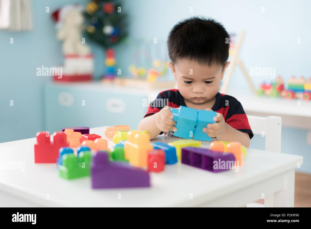 Adorable Asian Toddler baby boy sitting on chair and playing with color block toys at home. - Stock Image