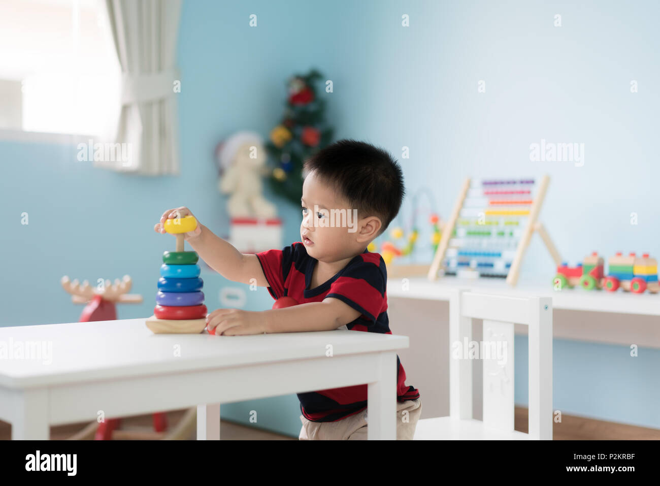 Adorable Asian Toddler baby boy sitting on chair and playing with color developmental toys at home. - Stock Image