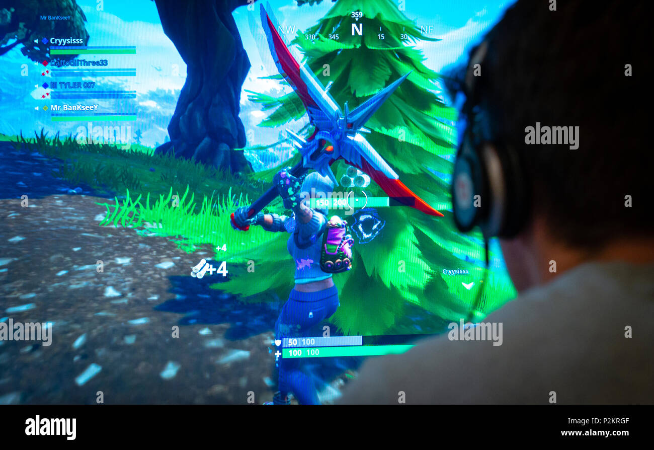Teenager playing Fortnite video game, Fortnite is an internet-based