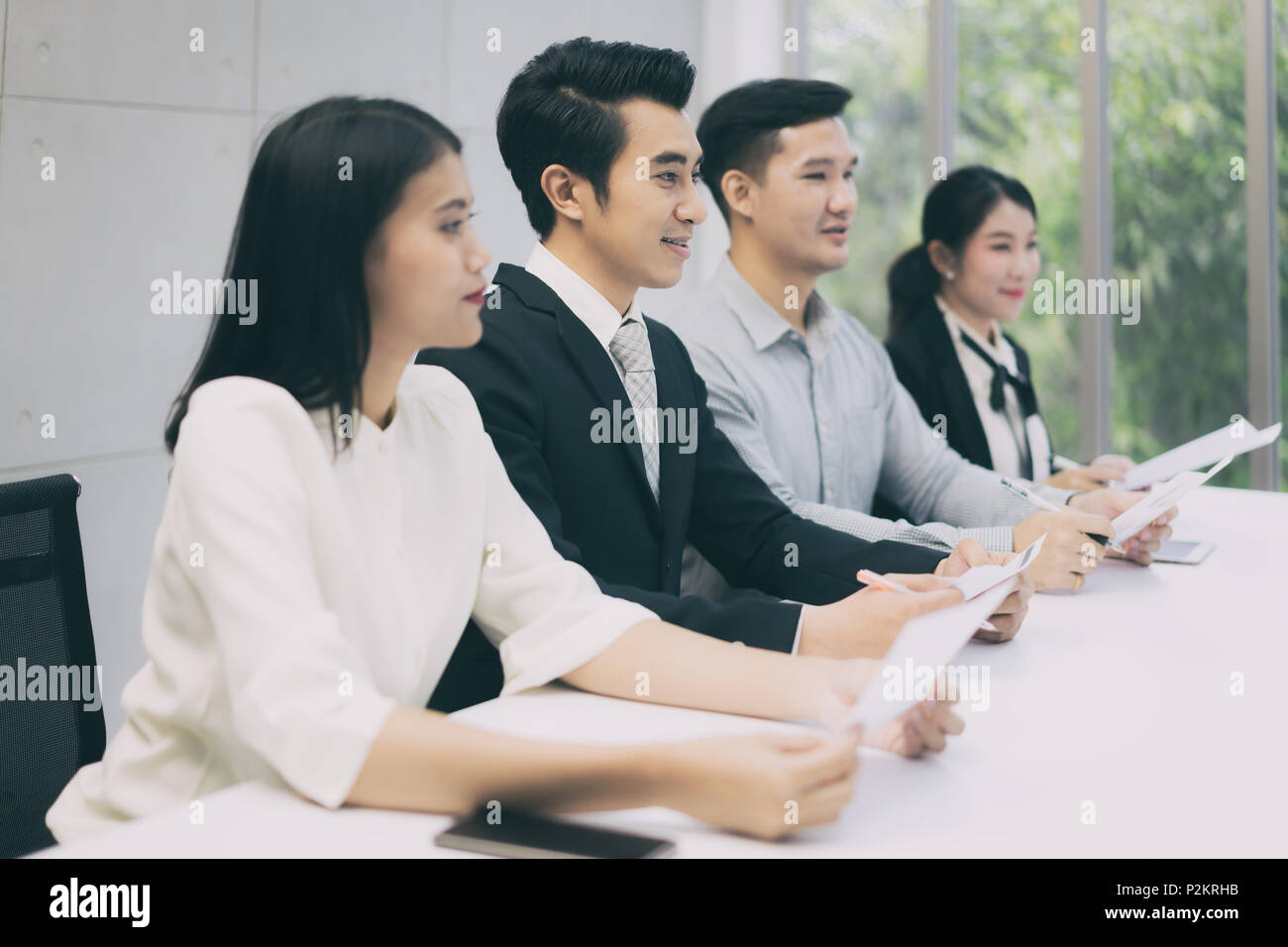 Cheerful business man sitting with other professionals waiting for job interview. Group of people waiting for job interview in office - Stock Image
