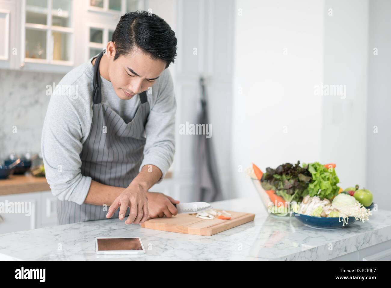 Asian confused man reading his tablet with a pensive thoughtful look while standing in his kitchen while cooking and preparing a meal from a variety o - Stock Image