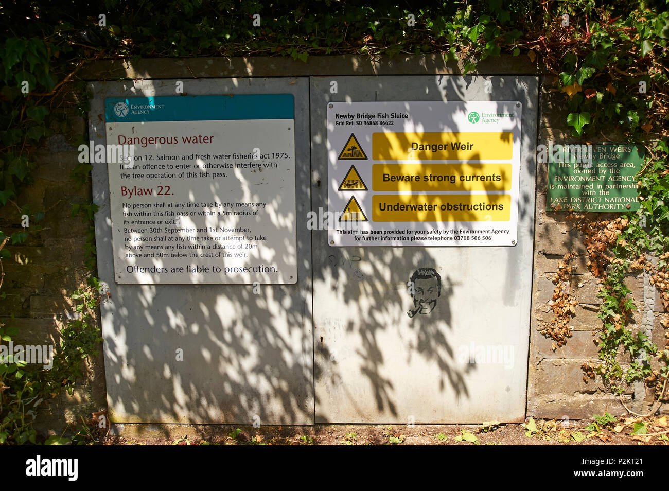 Warning signs on a fish ladder control box, in the Lake District National Park, Cumbria, England, UK,GB - Stock Image