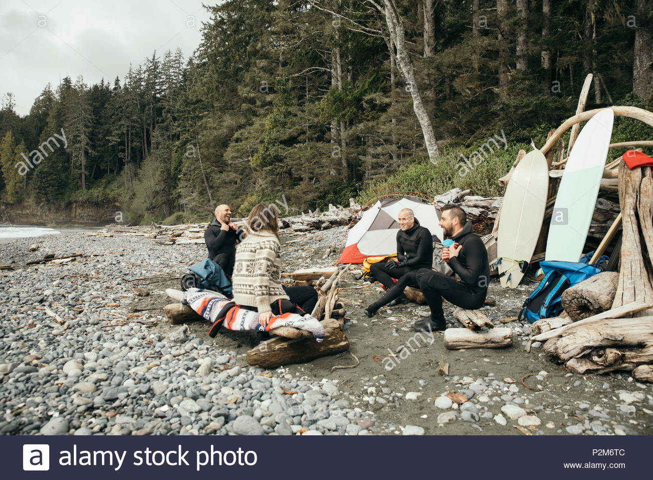 Friends enjoying weekend surfing getaway, relaxing at campsite on rugged beach - Stock Image