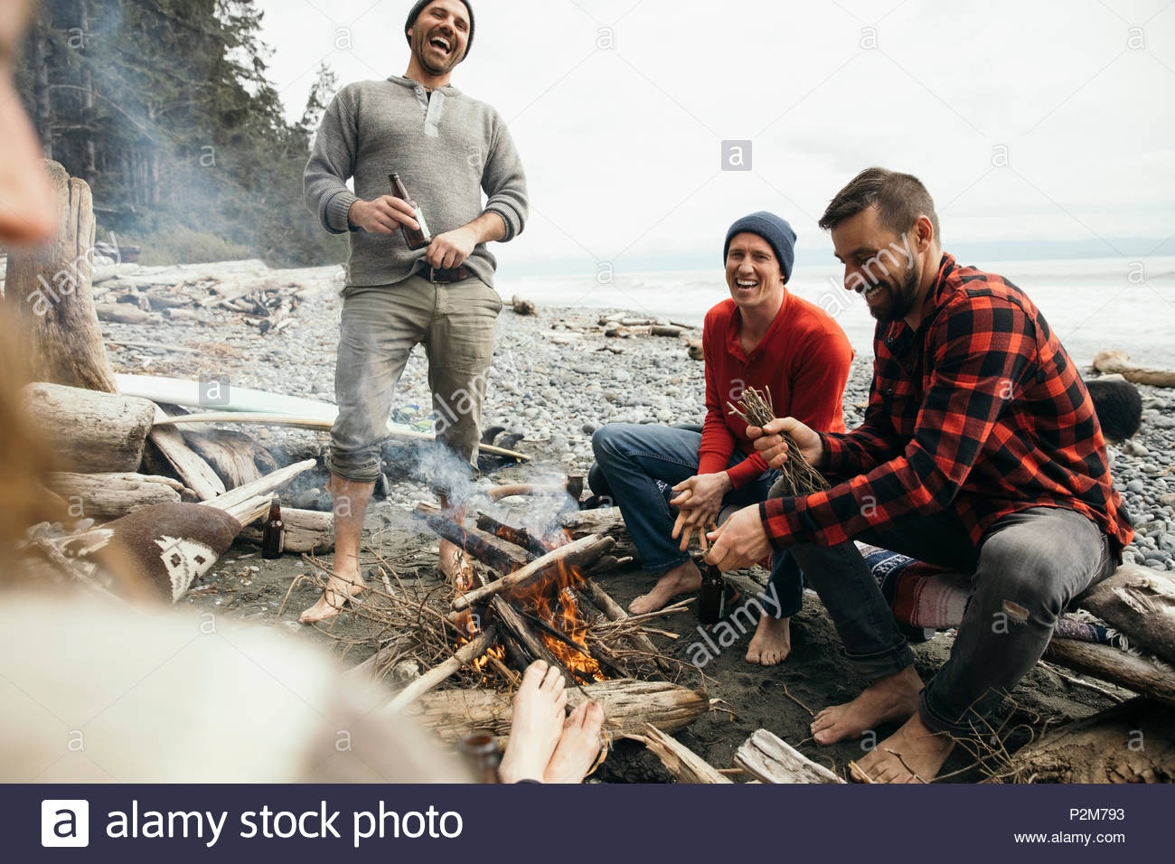 Barefoot friends enjoying beers by campfire on rugged beach - Stock Image
