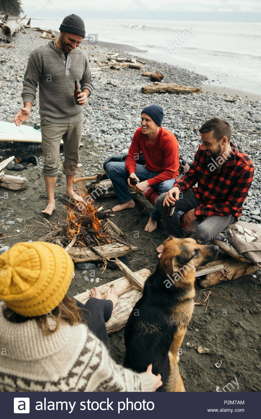 Friends enjoying beers, relaxing at campfire on rugged beach - Stock Image