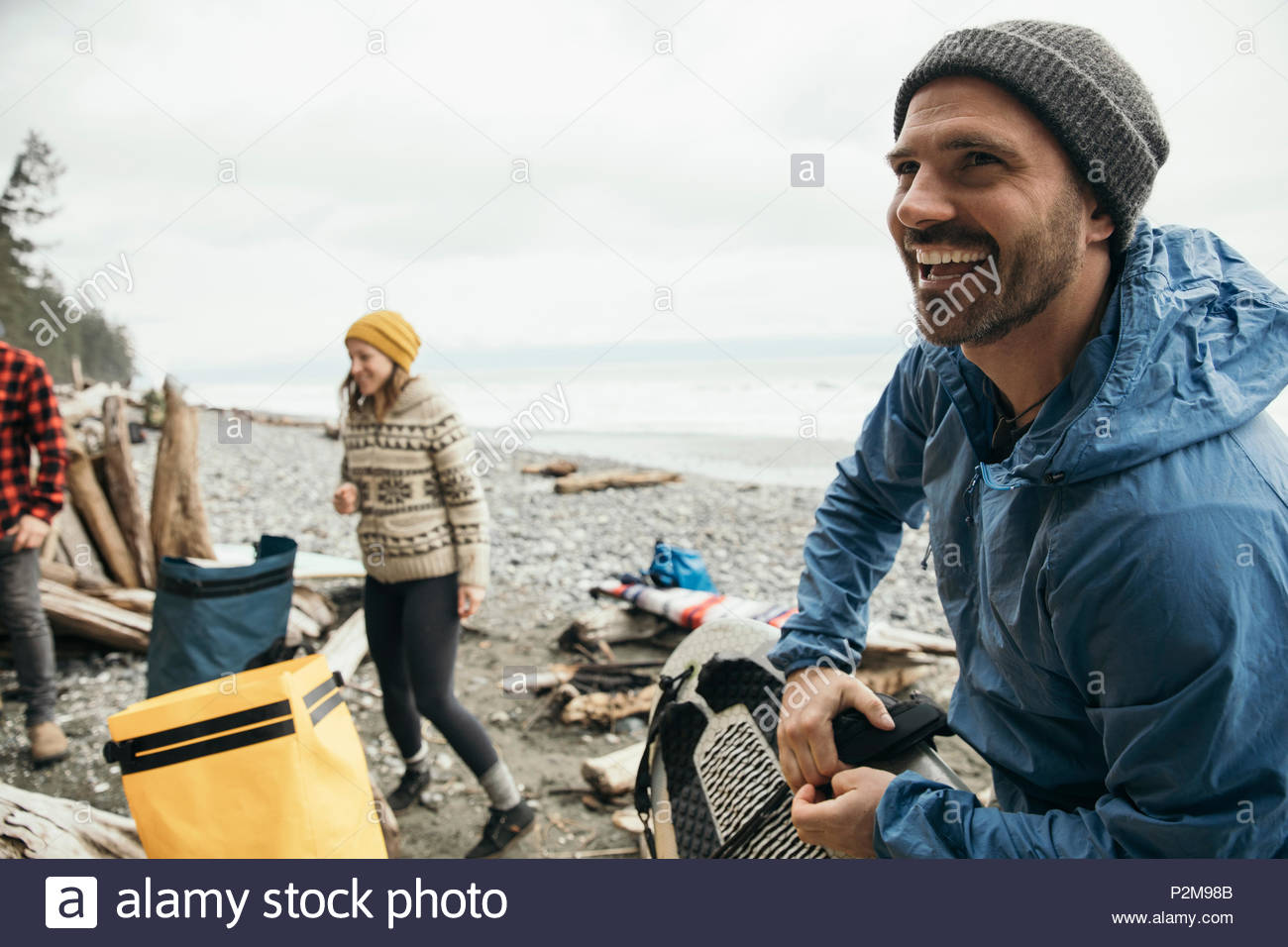 Smiling man enjoying weekend surfing getaway with friends on rugged beach - Stock Image