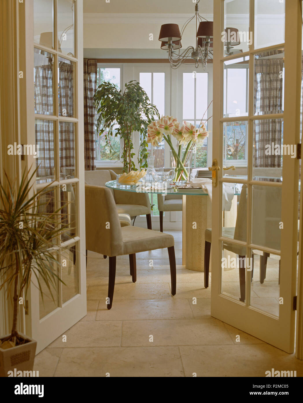 Glazed Double Doors Open To Modern Dining Room With Cream Upholstered Chairs At Glass Table