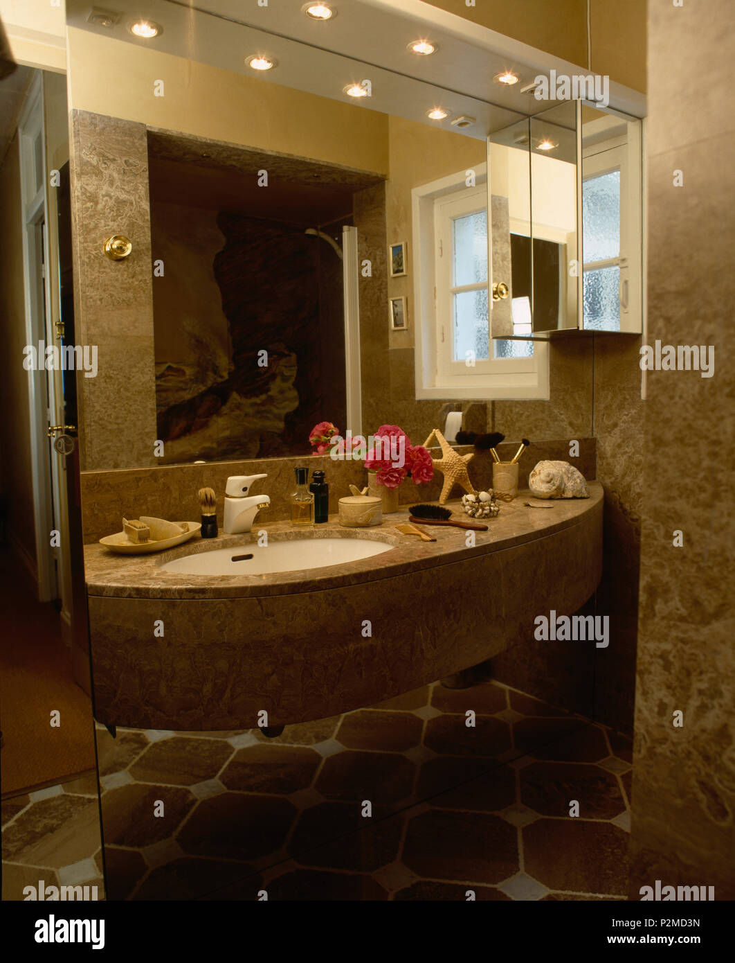 Recessed lighting and mirror above marble vanity unit with under-set basin in bathroom - Stock Image