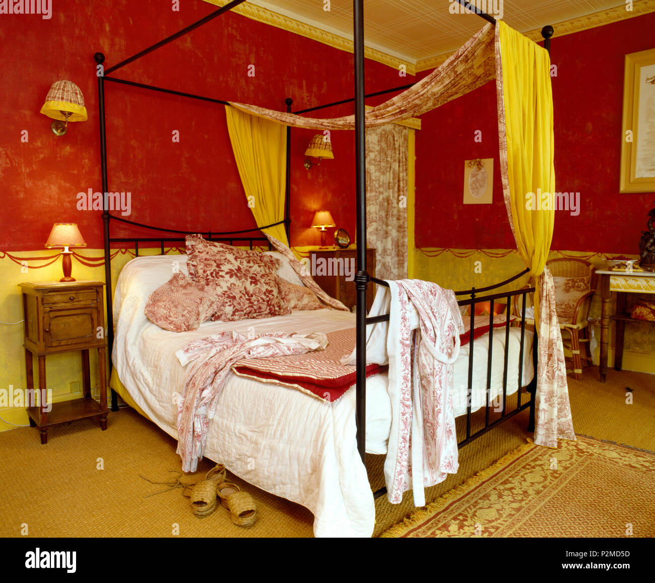 Toile-de-Jouy and yellow drapes on metal four-poster bed with white quilt and Toile-de-Jouy cushions in red French bedroom Stock Photo