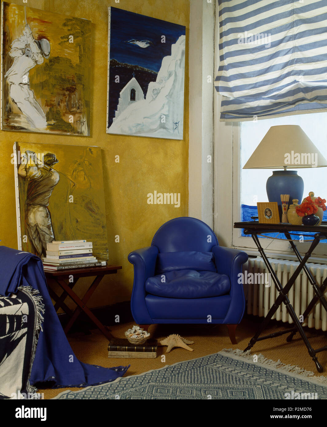 Large Paintings On Wall Above Bright Blue Leather Armchair In Corner Of  Living Room With Striped Blind On Window