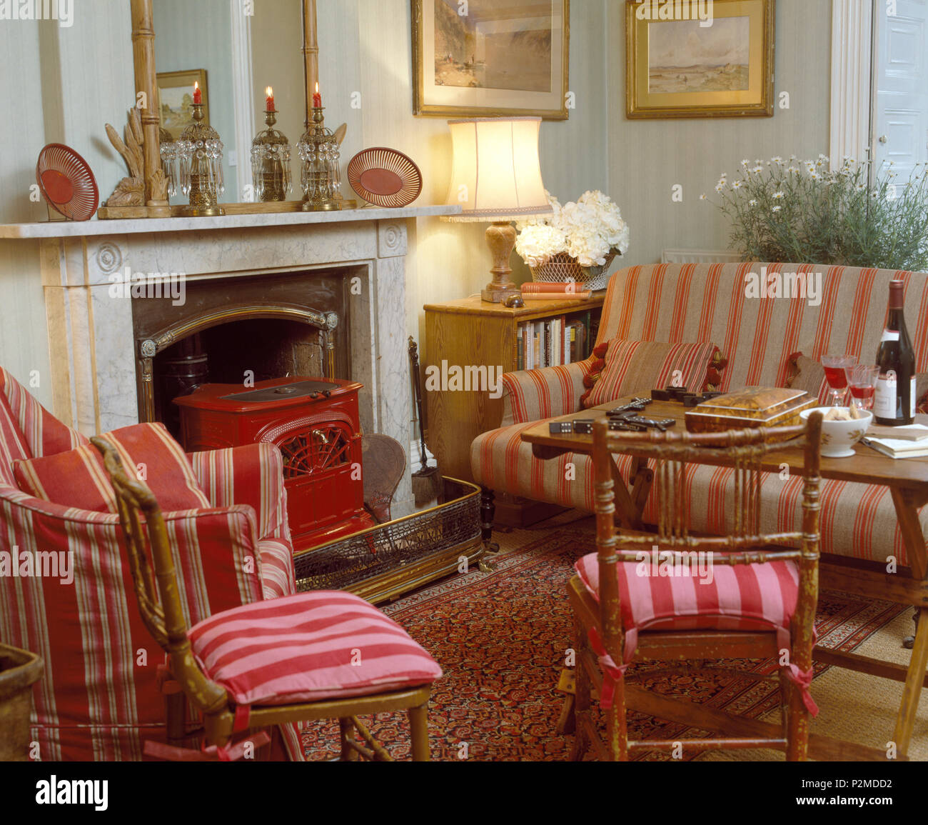 Striped red cushions on chairs and armchair beside fireplace with ...