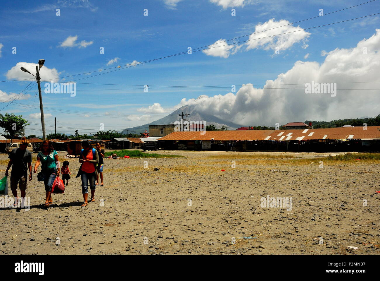 Indonesia. 15th June, 2018. The clear, blue sky was quickly turned grey with ash. In this shot, you can see the flows of dust and smoked sulfatara generated by the eruption. Seen fro kabanjahe city. Even with the relative size of the eruption, there is no chance this causes any climate impact. The initial estimates of sulfur released are too low to cause much atmosphere effects and the height of eruption wasn't tall enough to reach the stratosphere. Credit: Sabirin Manurung/Pacific Press/Alamy Live News - Stock Image