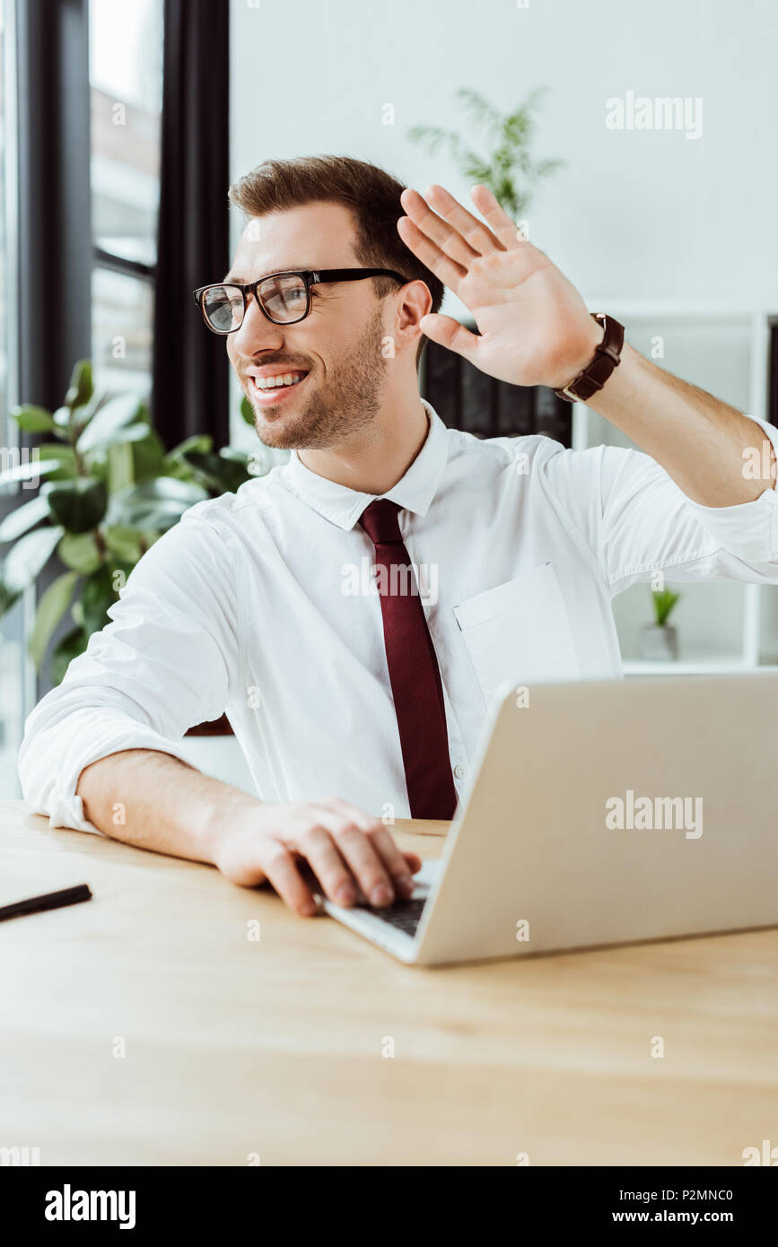smiling businessman working with laptop at workplace and waving to someone - Stock Image