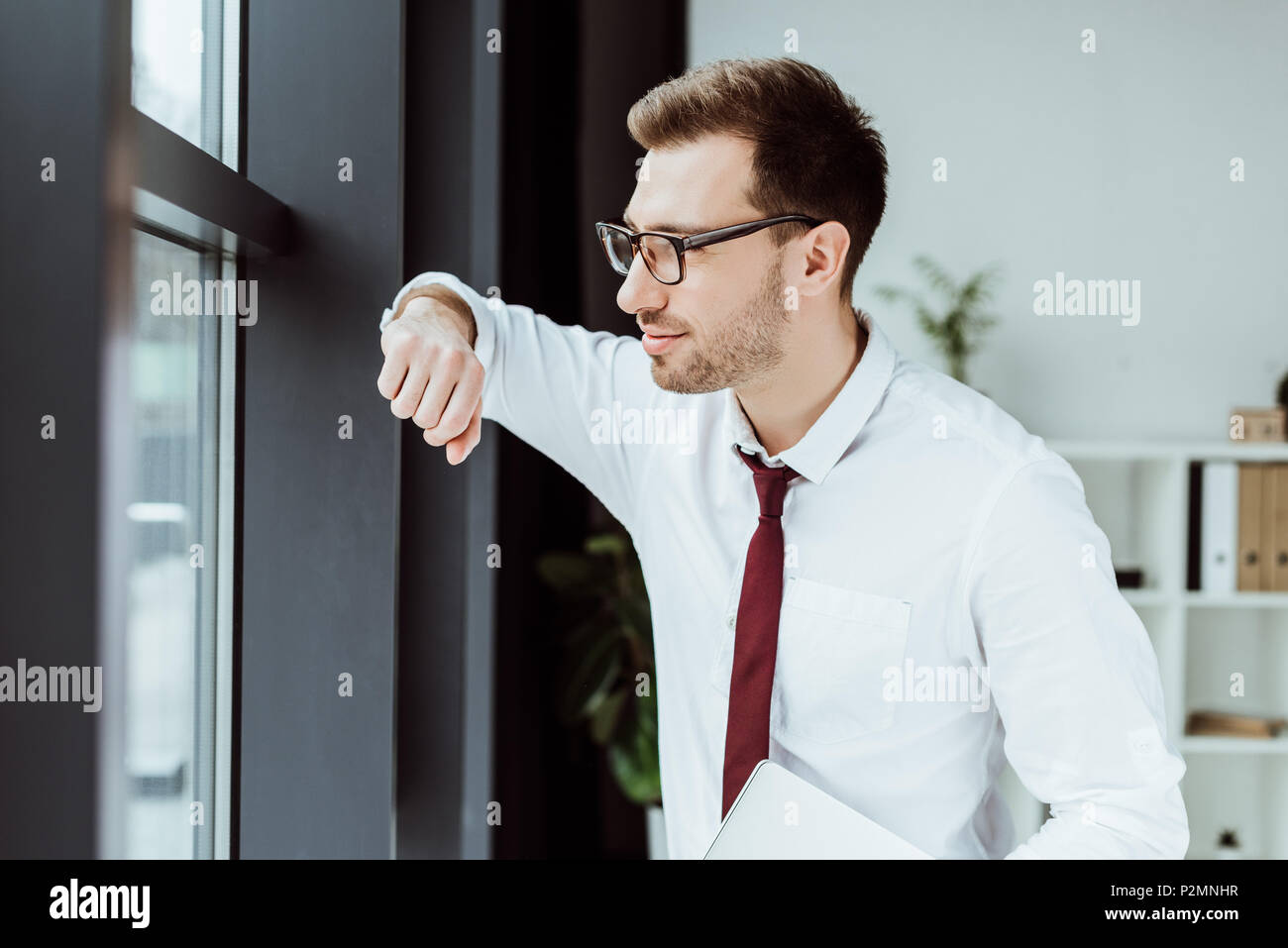 handsome stylish businessman with laptop looking at window in modern office - Stock Image