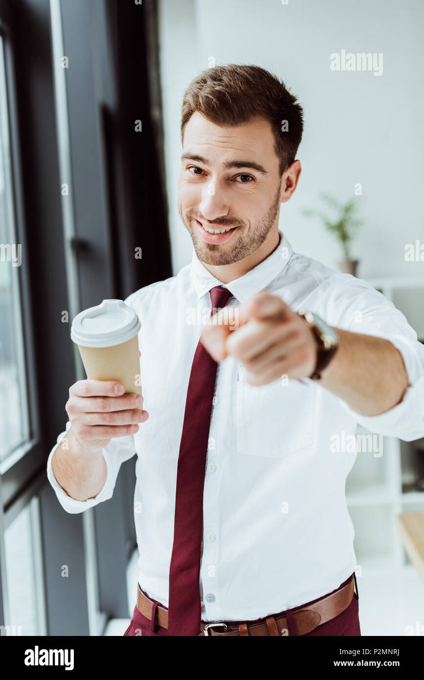 smiling businessman with disposable cup of coffee pointing at you - Stock Image