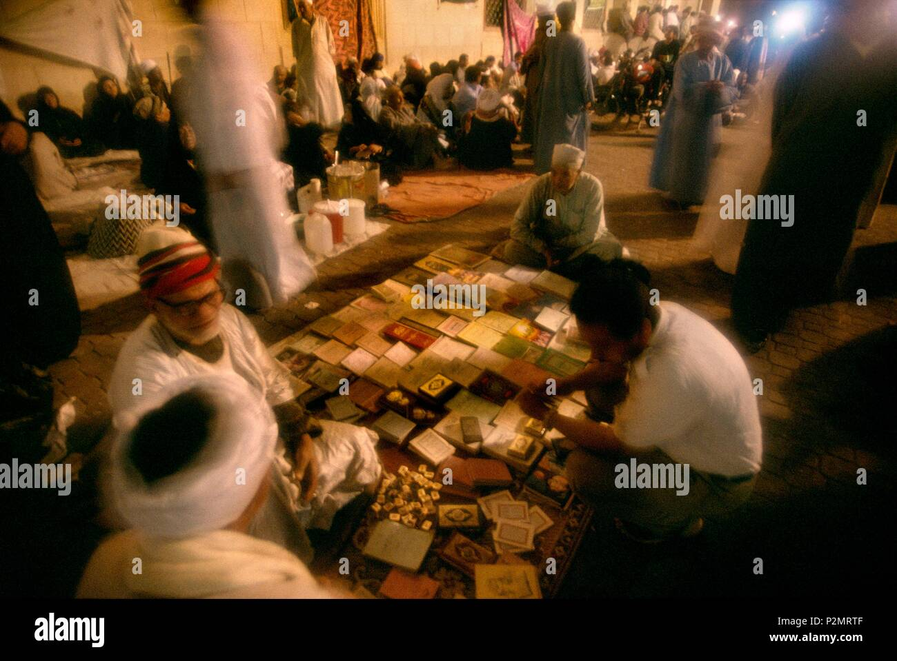 Egypt, Tanta, 1996, during the three days of festival (mouled) for Sidi Ahmad el-Badaoui, greatest Muslim saint of the country, pilgrims came with their families and get together on mats and carpets and sell books around Tanta's mosque - Stock Image