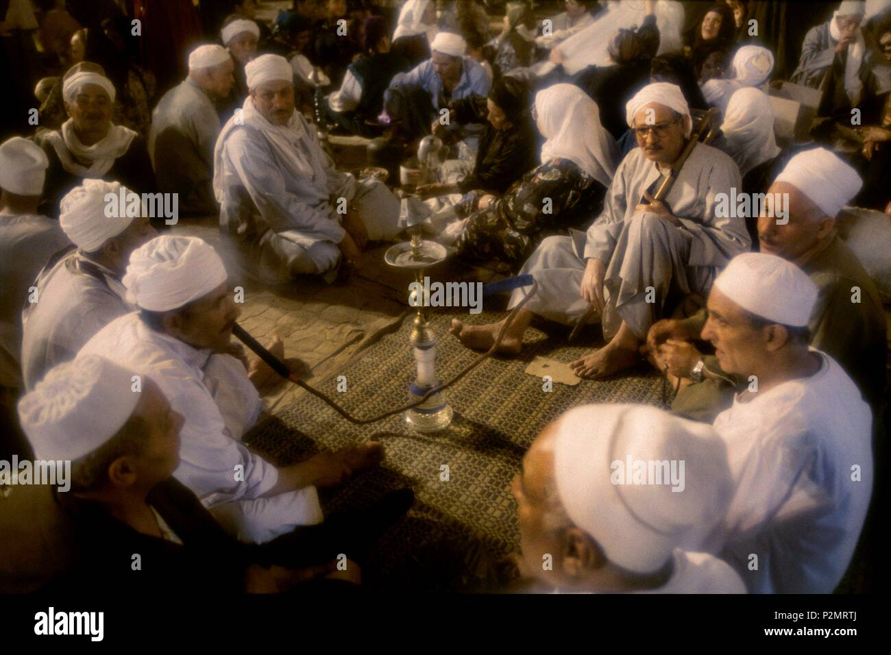 Egypt, Tanta, 1996, during the three days of festival (mouled) for Sidi Ahmad el-Badaoui, greatest Muslim saint of the country, pilgrims came with their families and get together on mats and carpets and eat, smoke hooka around Tanta's mosque - Stock Image