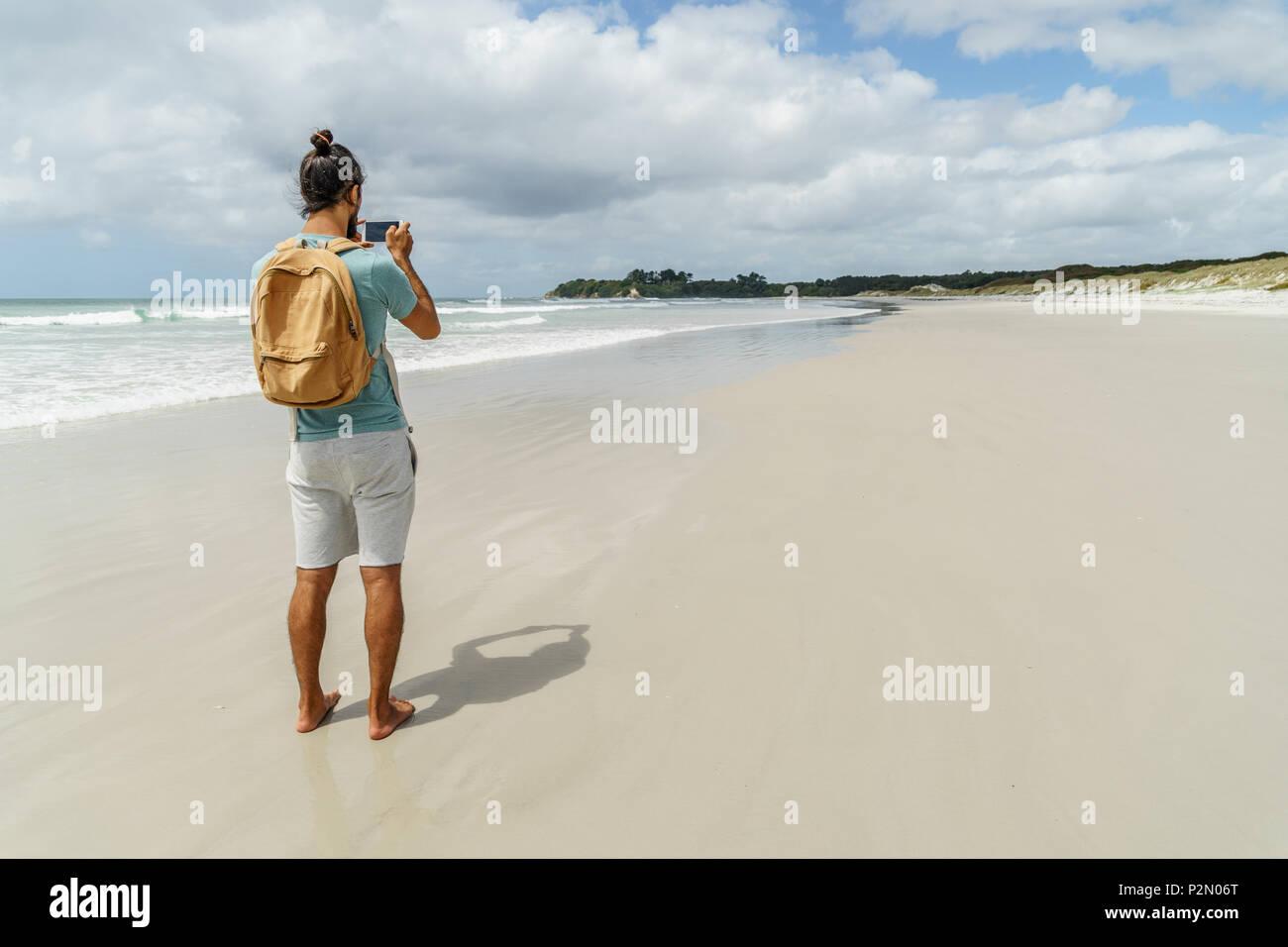rear view of man taking photo of coastline with smartphone, Rarawa beach, New Zealand - Stock Image