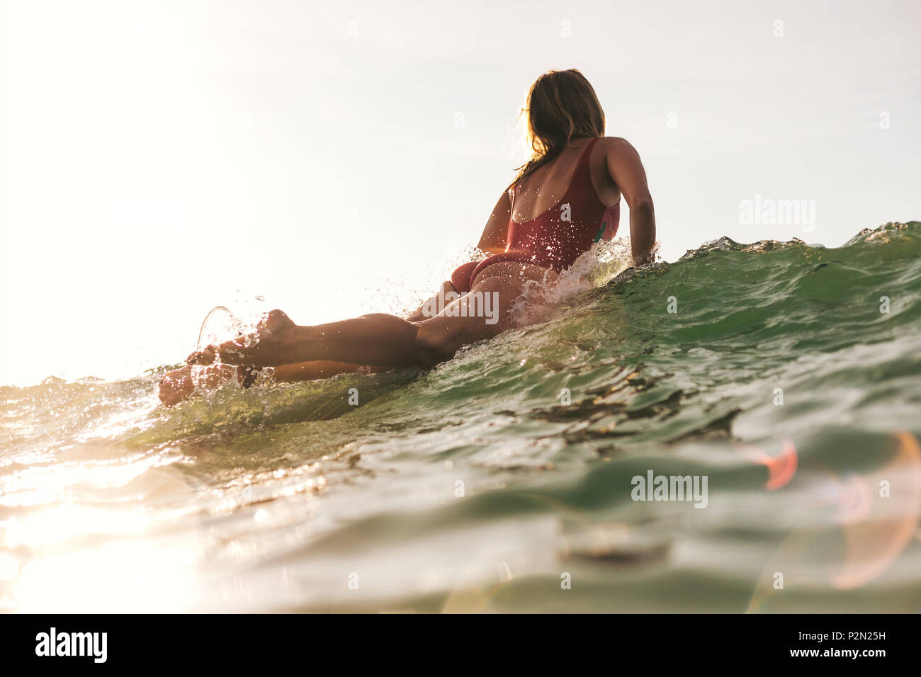 back view of woman in swimming suit surfing in ocean - Stock Image