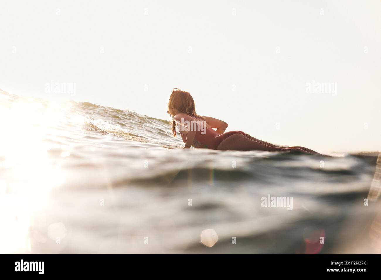 side view of woman in swimming suit surfing in ocean - Stock Image