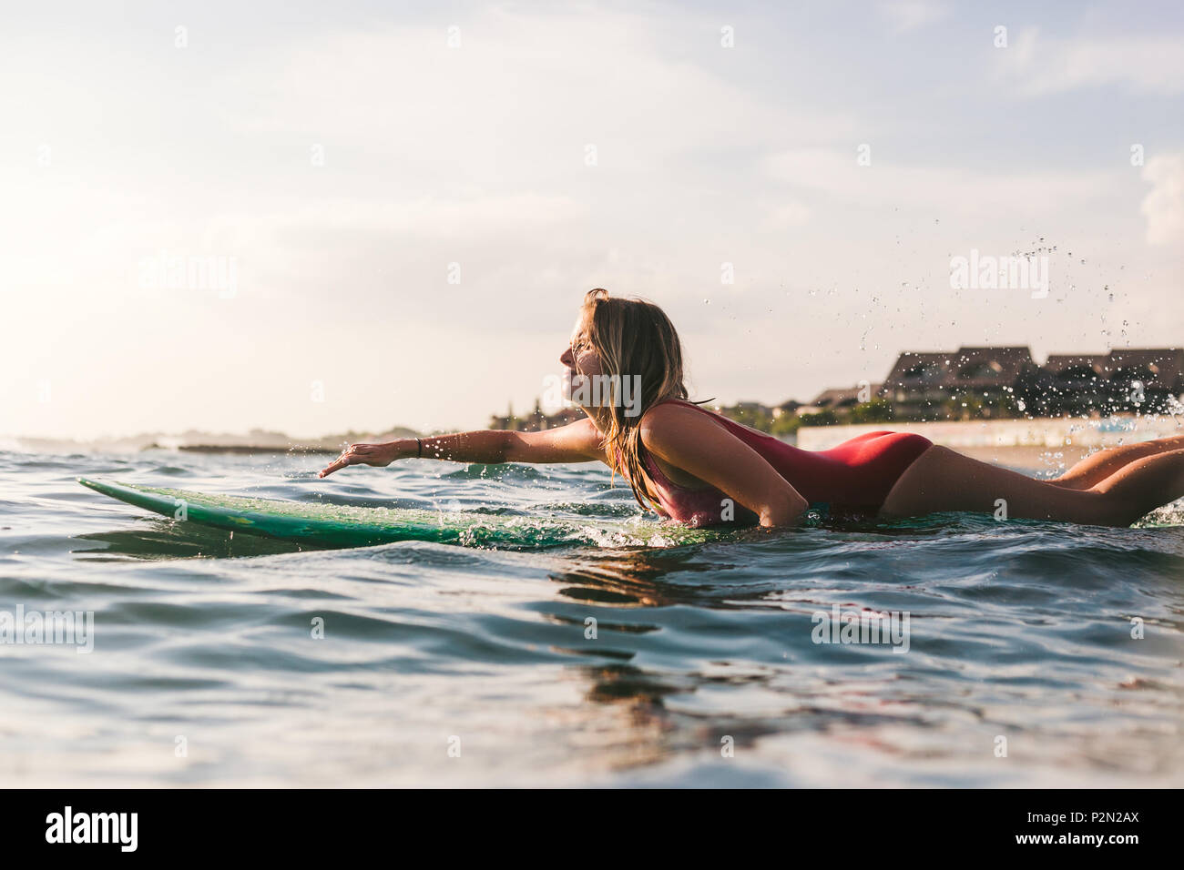 side view of young woman in swimming suit surfing alone in ocean - Stock Image