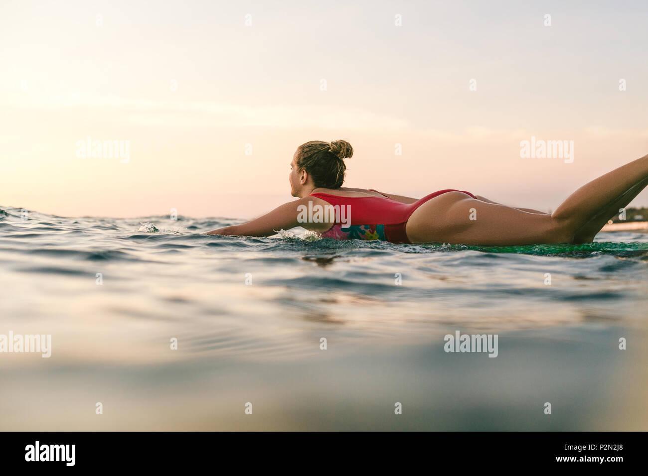 sportswoman in swimming suit surfing alone in ocean - Stock Image