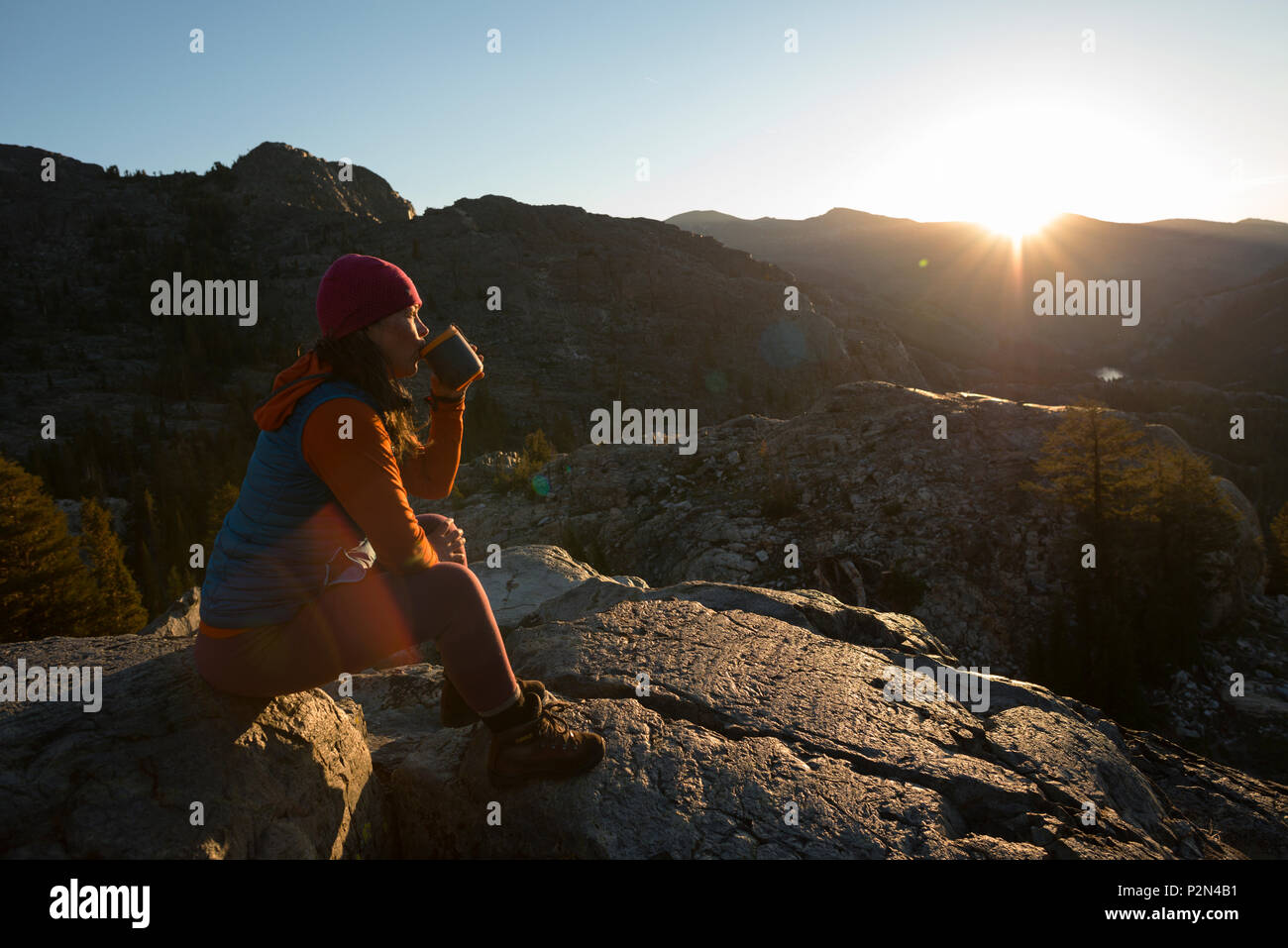 Woman drinking coffee at sunrise deep in the Ansel Adams Wilderness. High Sierra backpacking trip to Garnet Lake and Nydiver Lake. Stock Photo