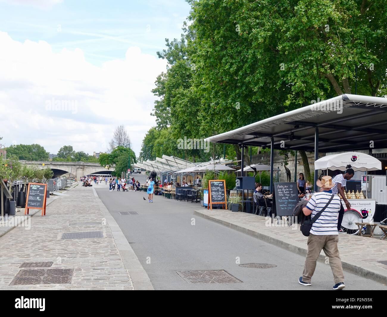 People walking, eating, drinking, working, along the riverside on the Rive Gauche, left bank, Promenade Berges de la Seine, Paris, France - Stock Image