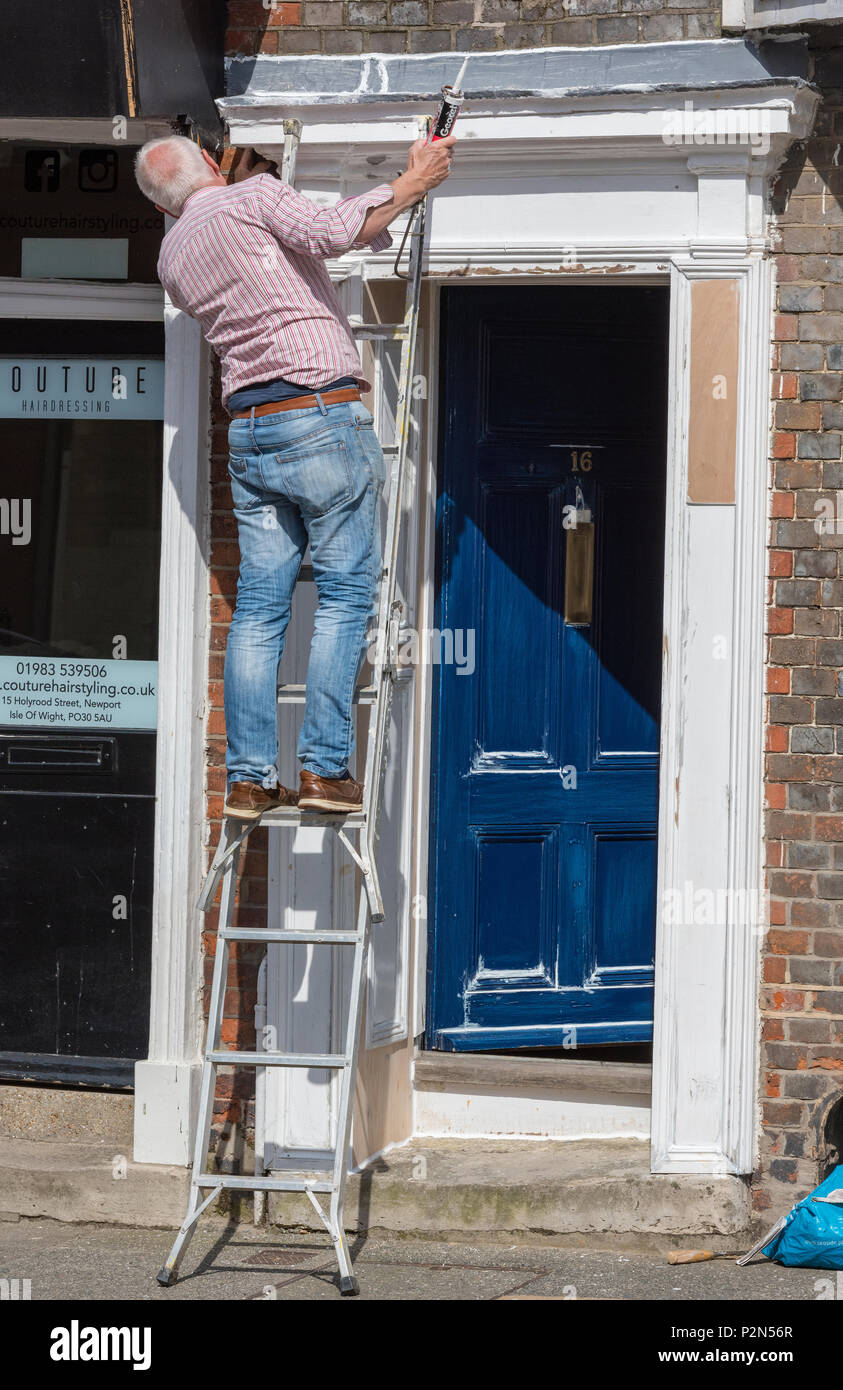 a man carrying out some diy and painting the front door on his home. man using a ladder to reach and access an area for painting on his home. DIY. - Stock Image