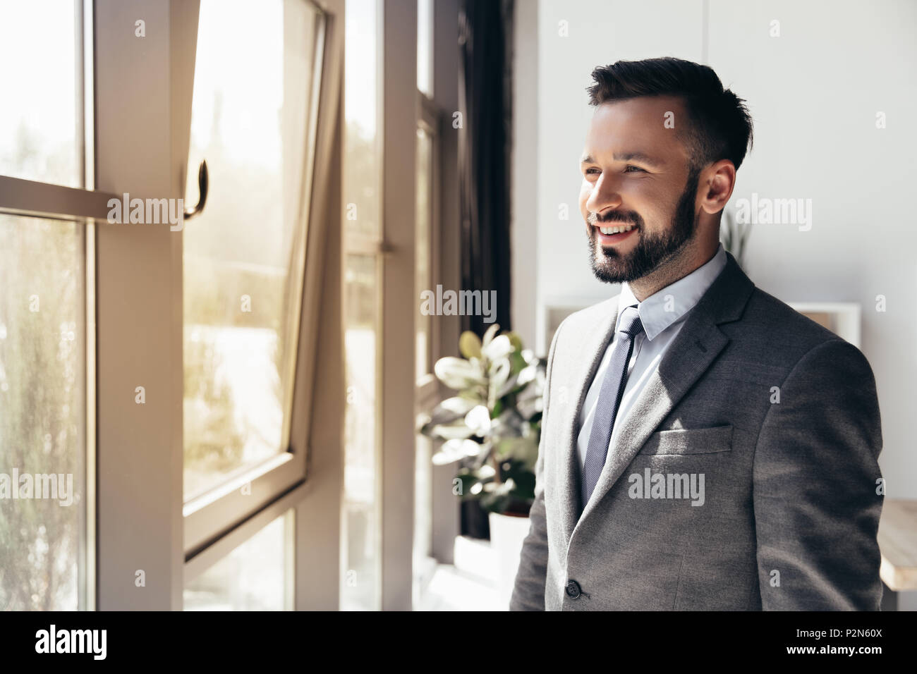 portrait of smiling businessman in formal wear looking away at modern office - Stock Image