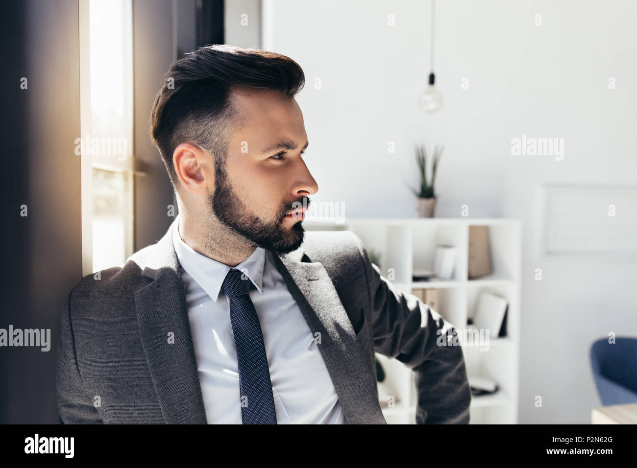 portrait of handsome businessman in formal wear looking away at modern office - Stock Image