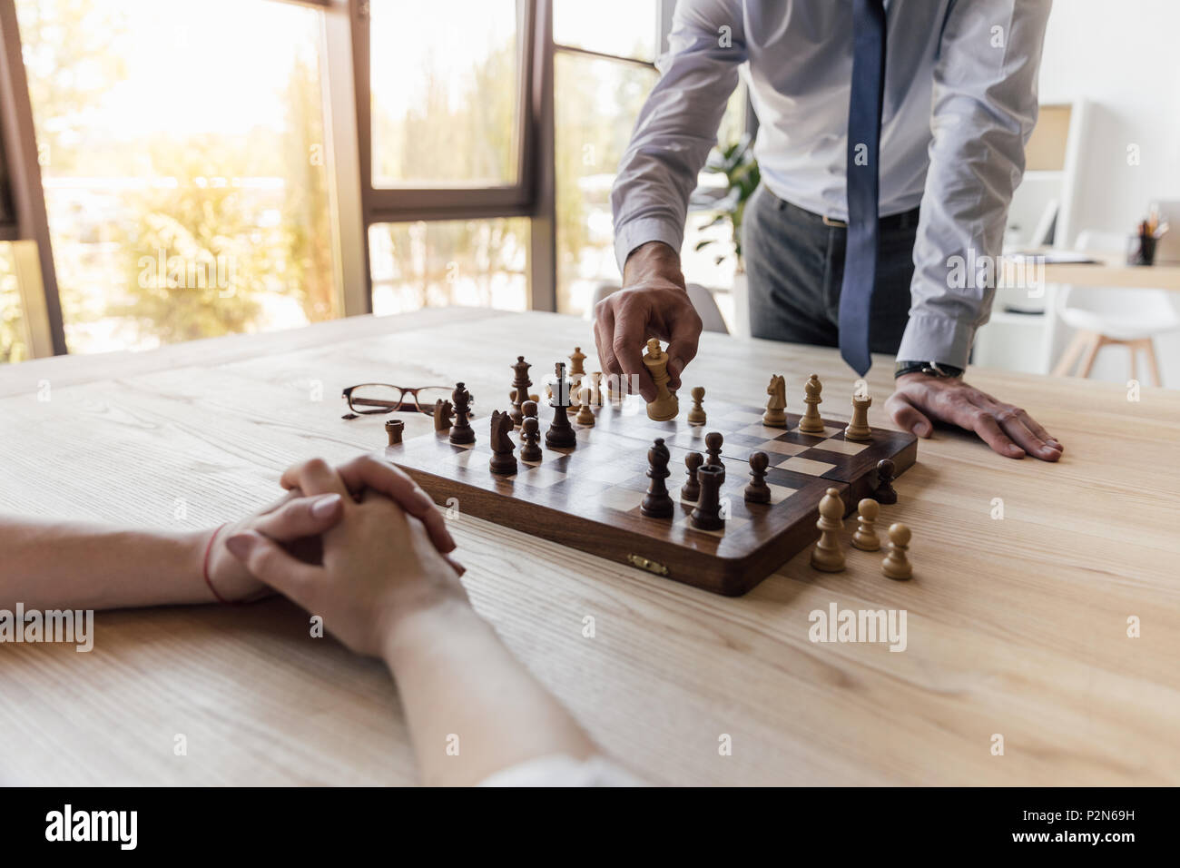 partial view of businessman playing chess with colleague in office - Stock Image